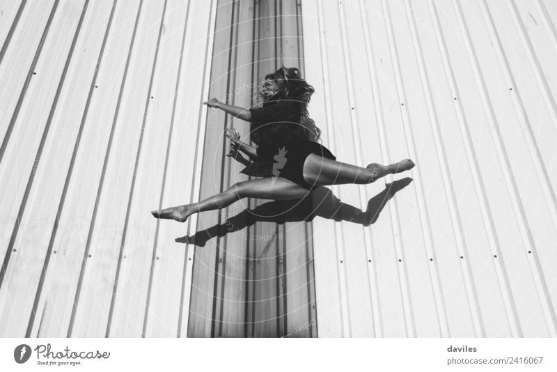Black and white portrait of dancer jumping and suspended, with an industrial wall in the background Lifestyle Leisure and hobbies Sports Fitness Sports Training
