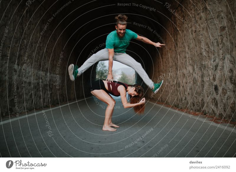 Man leapfrog jumping over woman on a road Joy Life Playing Freedom Human being Woman Adults Friendship Couple Youth (Young adults) 2 18 - 30 years Dancer Nature