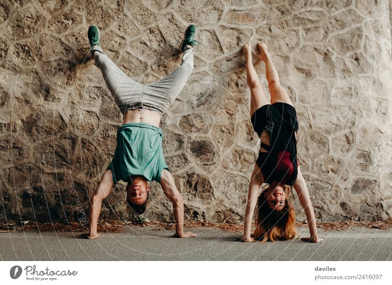 Young funny couple enjoying and doing a handstand Joy Happy Beautiful Human being Woman Adults Man Couple 2 18 - 30 years Youth (Young adults) Forest Street
