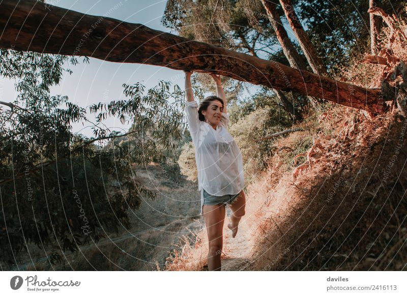 Smiling woman walking in nature and hanging from a fallen tree Lifestyle Mountain Hiking Human being Woman Adults 1 18 - 30 years Youth (Young adults) Nature