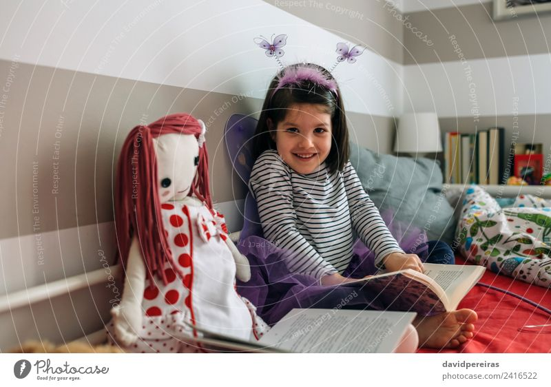 Girl disguised as a butterfly reading with her doll Lifestyle Happy Beautiful Playing Reading Lamp Bedroom Child Human being Woman Adults Friendship Infancy