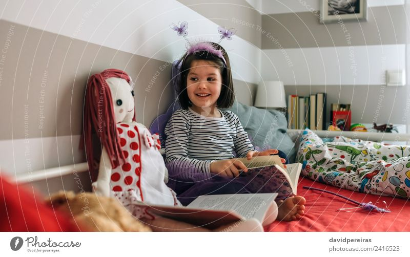 Girl disguised as a butterfly reading with her doll Woman Child Human being Beautiful Adults Lifestyle Funny Happy Small Playing Lamp Friendship Infancy Sit