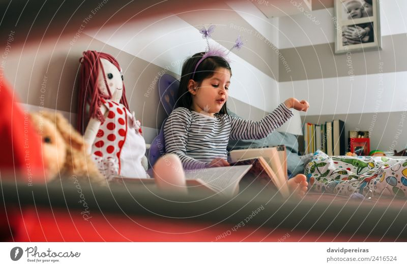 Girl disguised reading a book to her doll Lifestyle Happy Playing Reading Bedroom Child Human being Woman Adults Friendship Book Butterfly Wing Toys Smiling Sit