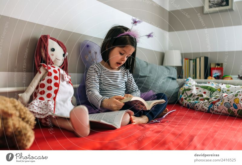 Girl disguised reading a book to her doll Woman Child Human being Beautiful Adults Lifestyle To talk Funny Small Playing School Friendship Sit Creativity