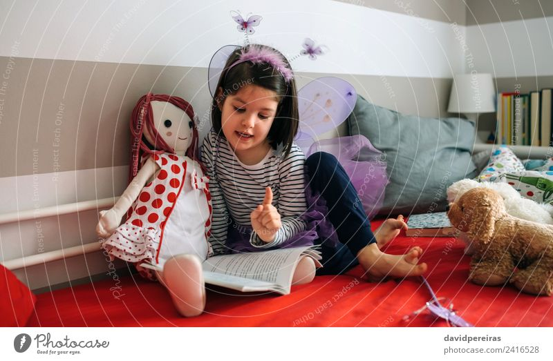 Girl disguised reading a book to her doll Woman Child Human being Beautiful Adults To talk Funny Small Playing Friendship Creativity Authentic Book Wing Cute