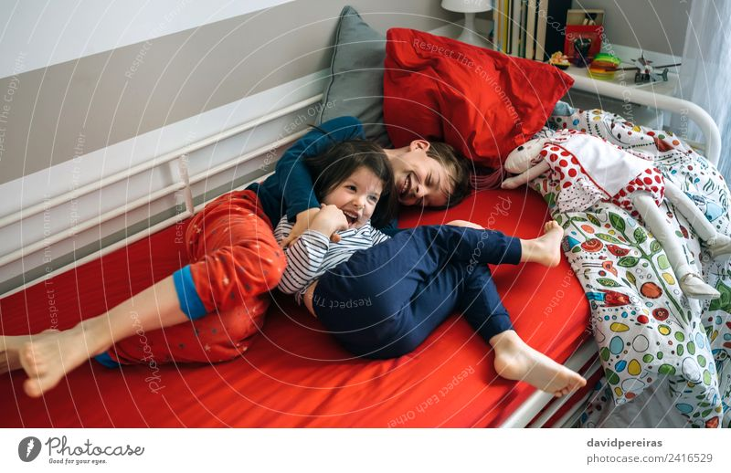 Brother and sister tickling and laughing on bed Lifestyle Joy Happy Playing Bedroom Child Human being Boy (child) Woman Adults Man Sister Family & Relations