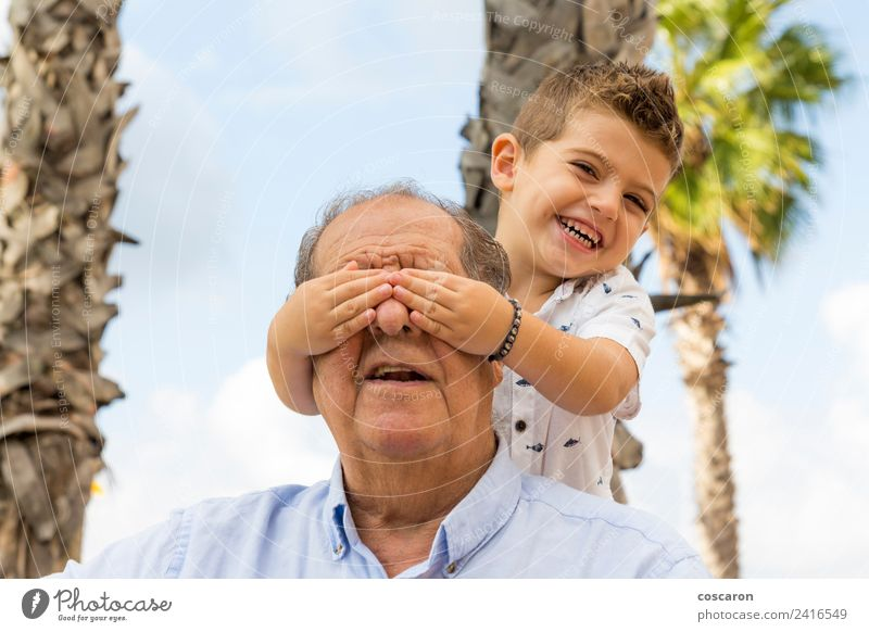 Grandson covering his granfather's eyes at park Lifestyle Happy Relaxation Leisure and hobbies Playing Child Retirement Boy (child) Man Adults Grandfather