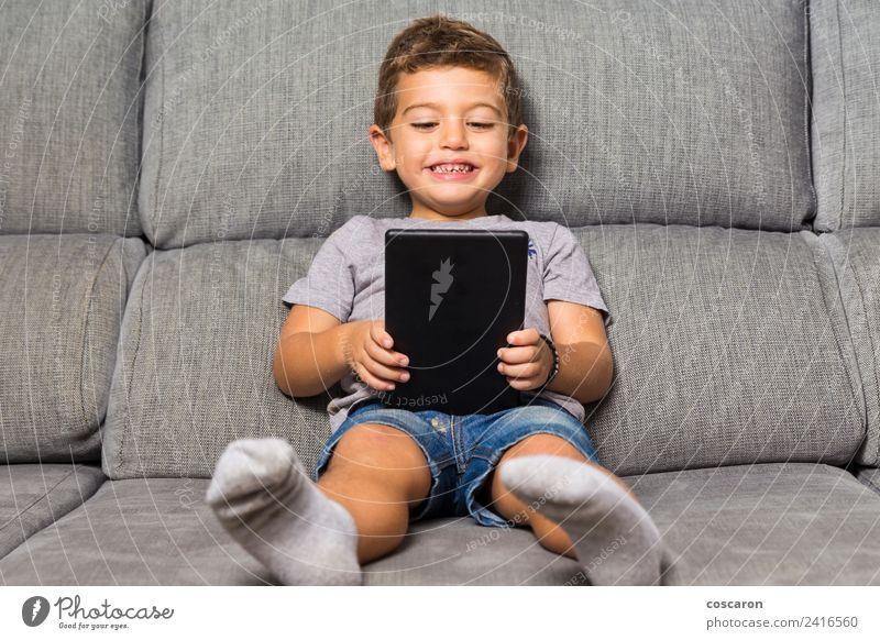 Little boy using a tablet Happy Leisure and hobbies Playing Sofa Child School Computer Notebook Screen Technology Internet Baby Toddler Boy (child) Infancy