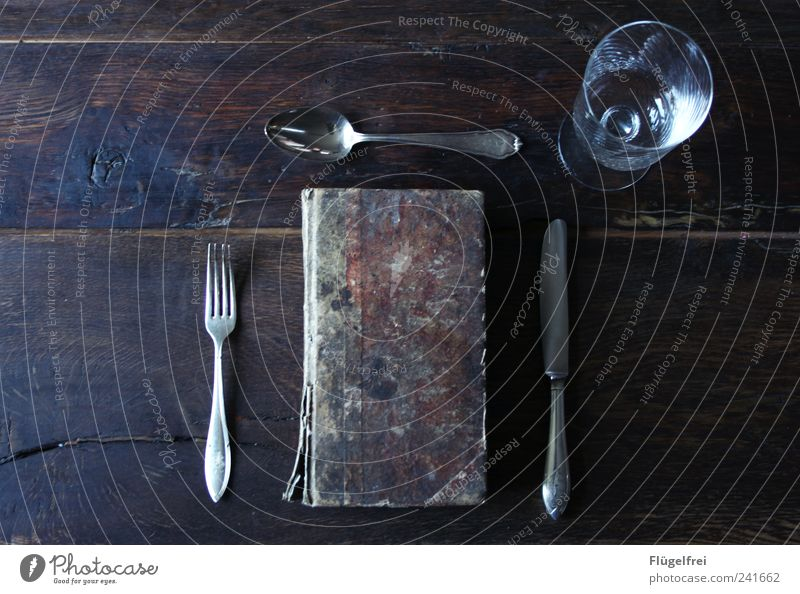 Book devouring - main course Cutlery Knives Fork Spoon Elegant Noble Ancient served Wine glass Arranged Dish Wooden table Structures and shapes Derelict