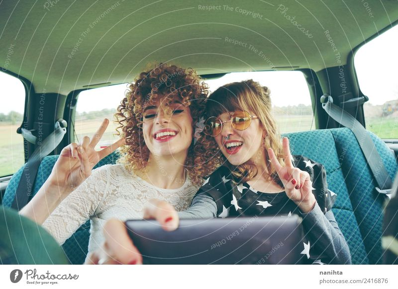 Two happy friends in a car making a selfie Lifestyle Style Joy Hair and hairstyles Vacation & Travel Tourism Trip Adventure Freedom Cellphone Camera Technology