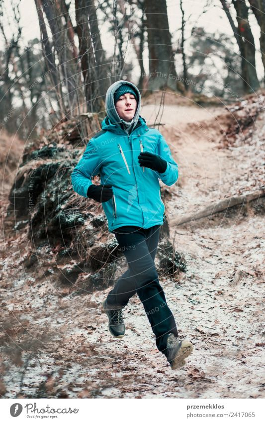 Young man running outdoors during workout in a forest Human being Nature Youth (Young adults) Man Tree Relaxation Joy Winter Forest Adults Lifestyle Healthy