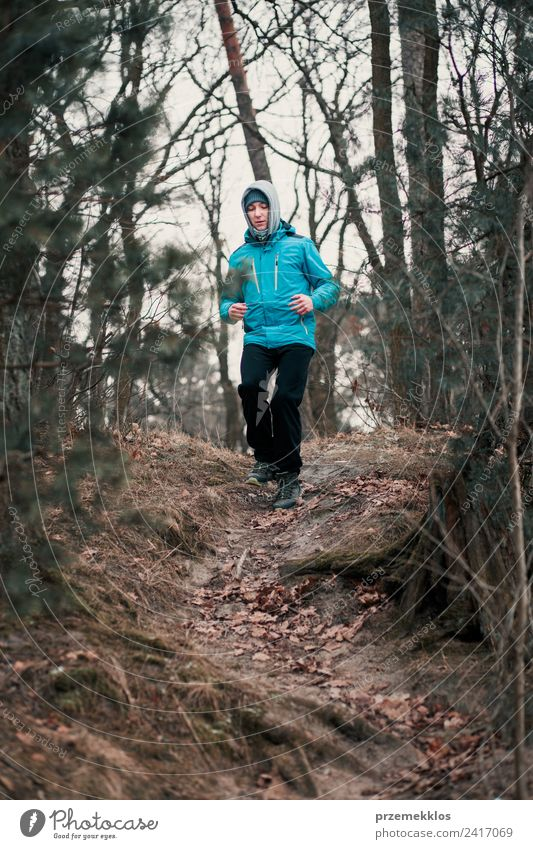 Young man running outdoors during workout in a forest Human being Nature Youth (Young adults) Man Tree Relaxation Joy Winter Forest Adults Lifestyle Autumn