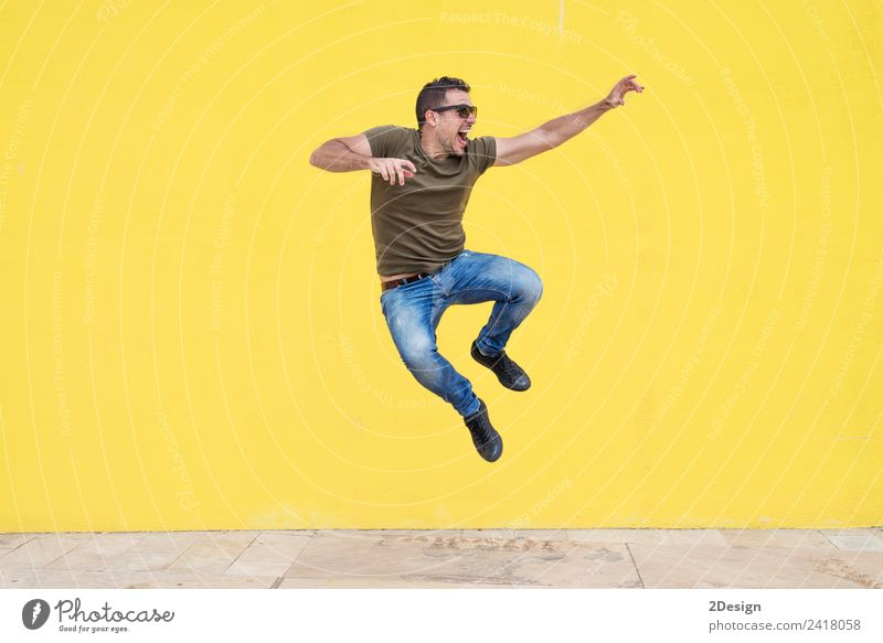 Young man with sunglasses jumping Lifestyle Joy Freedom Human being Masculine Youth (Young adults) Man Adults Arm 1 30 - 45 years Clothing T-shirt Jeans