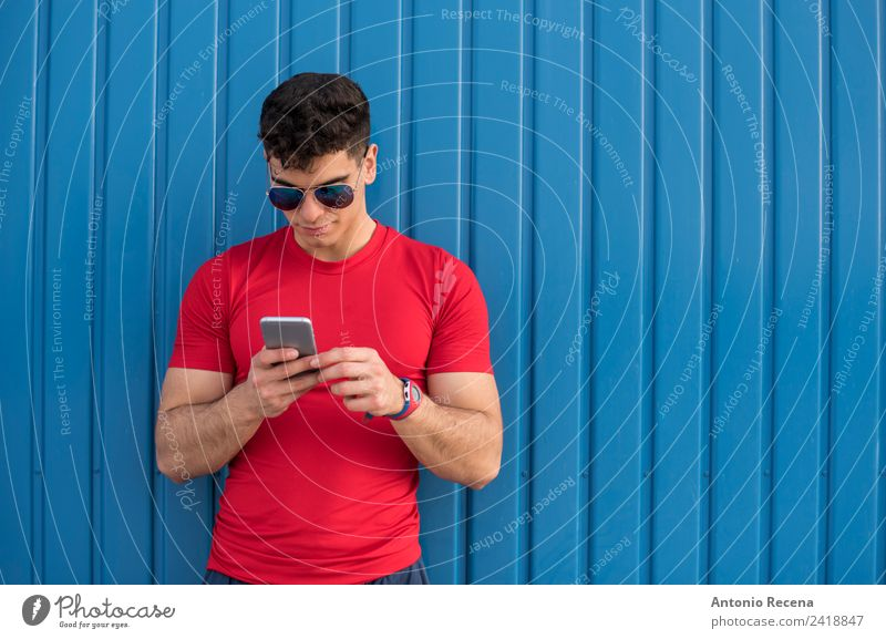 Red social on blue wall Reading Telephone PDA Human being Man Adults Sunglasses Brunette Touch Blue 20-25 years old 20s 30 years old attractive door Latin