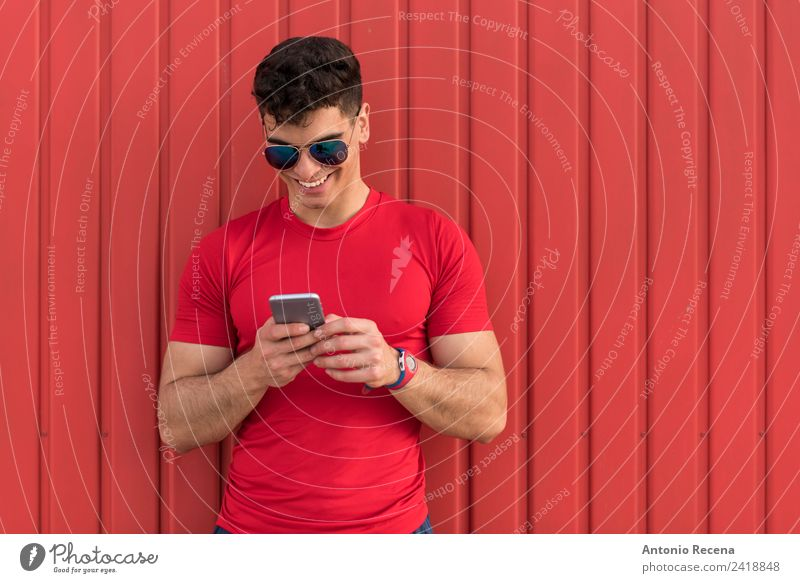 Man on red Reading Telephone Human being Adults Sunglasses Brunette Touch Smiling Red 20-25 years old 20s 30 years old attractive door Latin Latin American