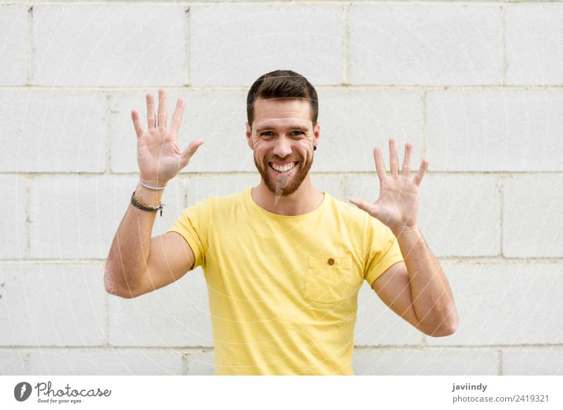 Funny young man on brick wall with open hands Human being Youth (Young adults) Man Young man Hand Joy 18 - 30 years Street Adults Lifestyle Yellow Laughter