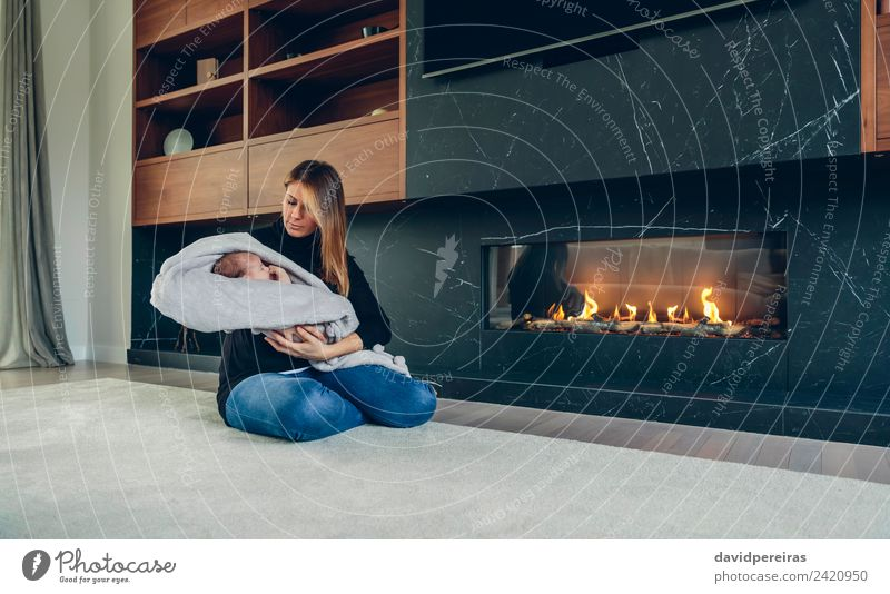 Mother hugging her baby in front of fireplace Lifestyle Happy Beautiful Furniture Fireside Living room Child Human being Baby Woman Adults Family & Relations