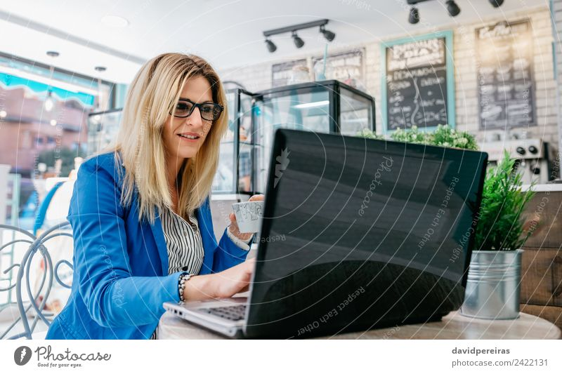 Woman drinking coffee and chatting with the laptop Reading Work and employment Workplace Computer Notebook Internet Human being Adults Plant Blonde Driving
