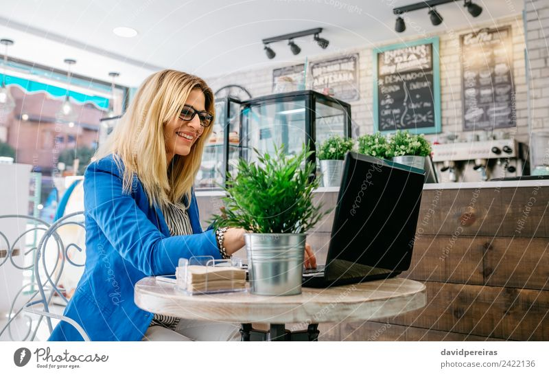 Businesswoman using the laptop Happy Reading Work and employment Workplace Computer Notebook Internet Human being Woman Adults Plant Blonde Driving To enjoy