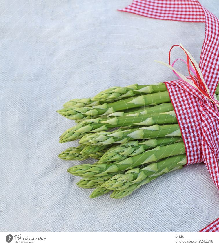 A portion of green asparagus tips, freshly harvested from the local field, tied together and decorated with a ribbon with a bow, made of checked fabric, on the table with white linen cloth.