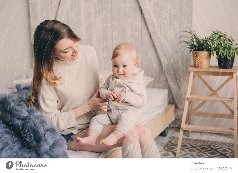 c6447a21d happy mother and baby playing at home in bedroom - a Royalty Free ...