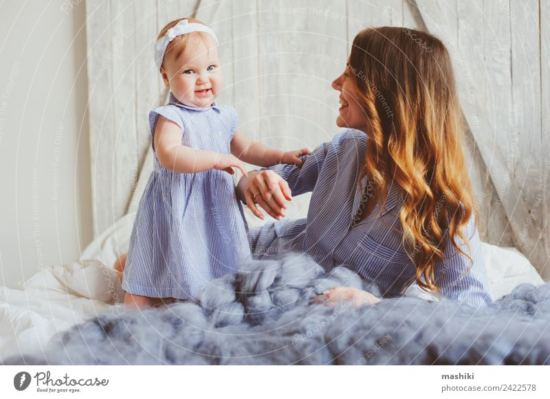 happy mother and 9 month old baby in matching pajamas Lifestyle Joy Playing Bedroom Baby Parents Adults Mother Family & Relations Infancy Hand Stripe Embrace