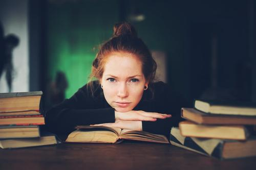 indoor portrait of thoughtful or sad woman learning Woman Relaxation Dark Black Adults Lifestyle Sadness Wood Gray Dream Modern Book Academic studies Reading