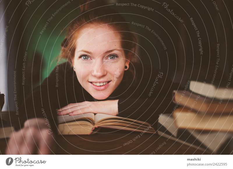 indoor portrait of redhead happy woman learning Lifestyle Relaxation Reading Table Academic studies Woman Adults Book Library Sweater Red-haired Study Dream