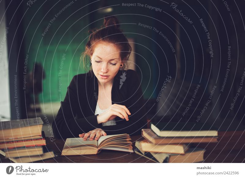 indoor portrait of thoughtful or sad student learning Lifestyle Relaxation Reading Table Academic studies Woman Adults Book Library Sweater Red-haired Dream