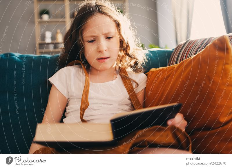 concentrated child girl reading interesting book at home Lifestyle Relaxation Reading Child Schoolchild Infancy Book Library Authentic Small Smart Home kid
