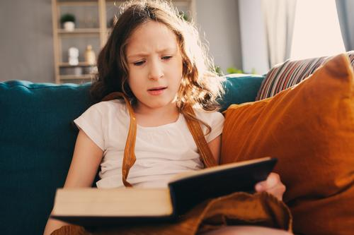 concentrated child girl reading interesting book at home Child Relaxation Lifestyle Small Infancy Authentic Book Reading Home Story Cozy Fairy tale Smart