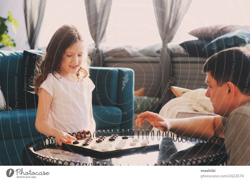 child girl playing checkers with her dad Lifestyle Joy Leisure and hobbies Playing Chess Success Child Parents Adults Father Family & Relations Toys Think