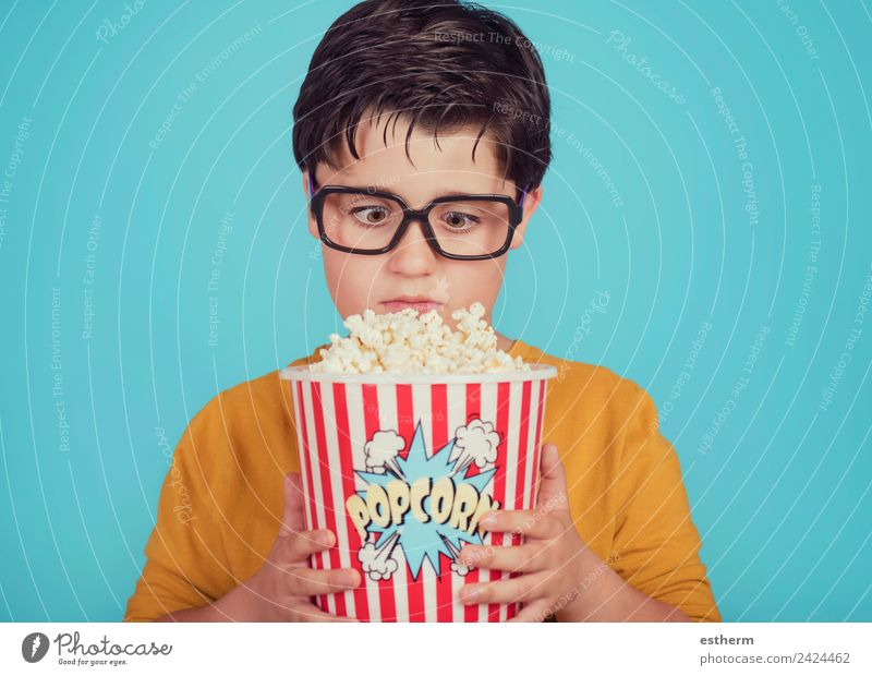 little boy child with popcorn on blue background Child Human being Eating Lifestyle Funny Emotions Movement Boy (child) Food Leisure and hobbies Masculine