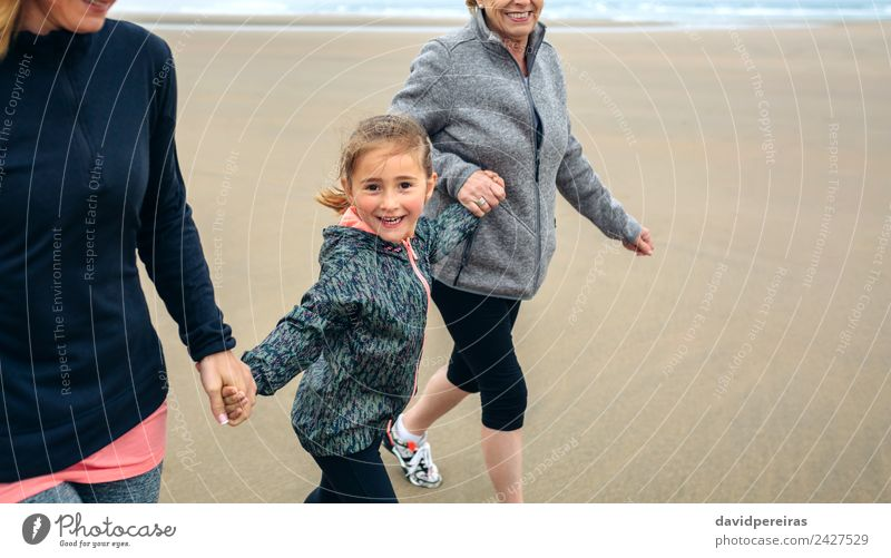 Girl running with two women on the beach Lifestyle Joy Happy Playing Beach Child Human being Woman Adults Mother Grandmother Family & Relations Sand Autumn Fog