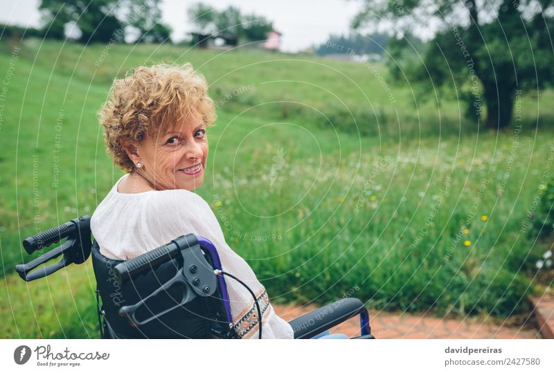 Smiling senior woman in wheelchair Happy Health care Relaxation Garden Retirement Human being Woman Adults Grandmother Nature Plant Tree Grass Old Sit Authentic