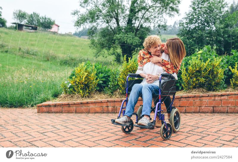 Daughter hugging her senior mother in wheelchair Woman Human being Nature Old Plant Tree Relaxation Loneliness Adults Lifestyle Love Health care