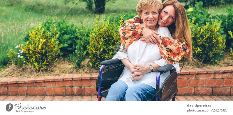 Daughter embracing senior mother in wheelchair Lifestyle Happy Health care Relaxation Garden Human being Woman Adults Mother Grandmother Family & Relations