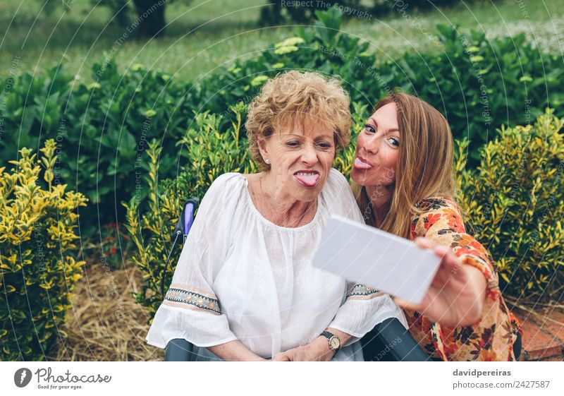 Woman taking selfie with older mother in wheelchair Lifestyle Joy Happy Health care Garden PDA Human being Adults Mother Grandmother Family & Relations Nature