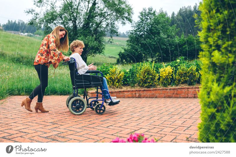 Woman carrying her mother in a wheelchair Lifestyle Happy Health care Relaxation Garden To talk Human being Adults Mother Grandmother Family & Relations Nature