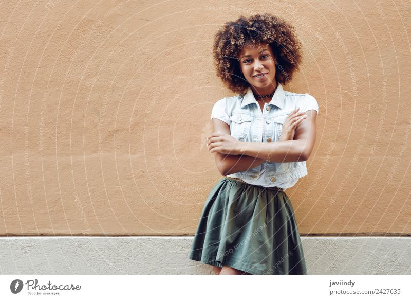 Black woman, afro hairstyle, smiling near a wall outdoors Lifestyle Style Happy Beautiful Hair and hairstyles Face Human being Young woman Youth (Young adults)