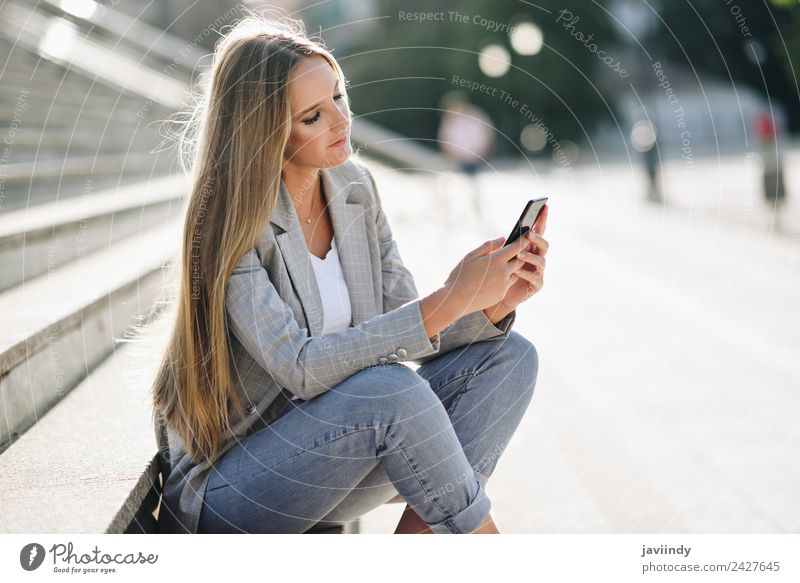 Blonde woman looking at her smartphone outdoors Lifestyle Style Beautiful Hair and hairstyles Telephone PDA Human being Young woman Youth (Young adults) Woman