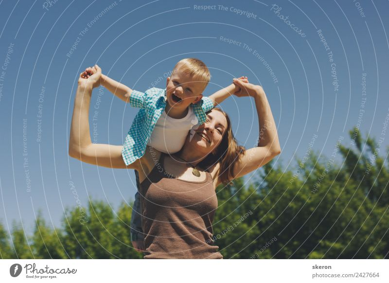 happy family: a young mother takes her child on her shoulder Child Human being Nature Youth (Young adults) Young woman Landscape Tree 18 - 30 years Face Street