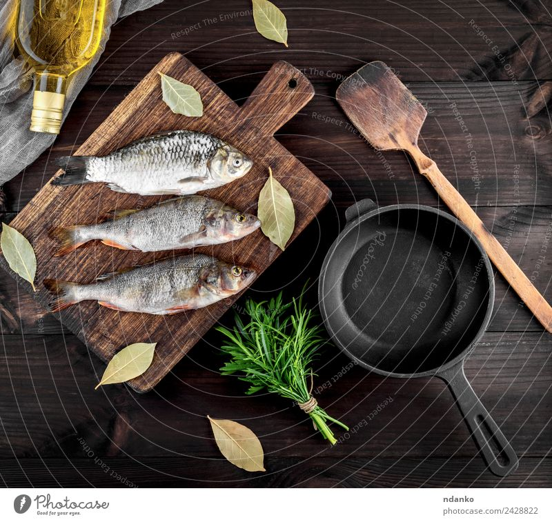 three river fish on a brown wooden board Fish Seafood Herbs and spices Nutrition Dinner Diet Pan Table Wood Eating Dark Fresh Above Retro Brown Black Perches