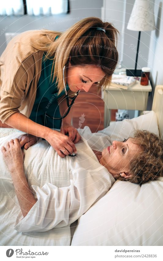 Caregiver auscultating senior woman Health care Illness House (Residential Structure) Lamp Doctor Hospital Human being Woman Adults Heart Old Listening