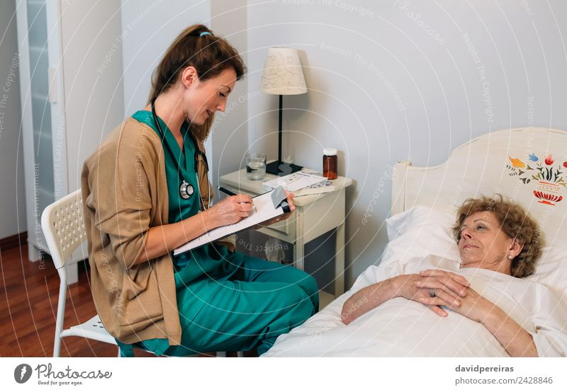 Female doctor filling out a questionnaire Health care Medical treatment Illness Medication House (Residential Structure) Lamp Chair Doctor Hospital Human being
