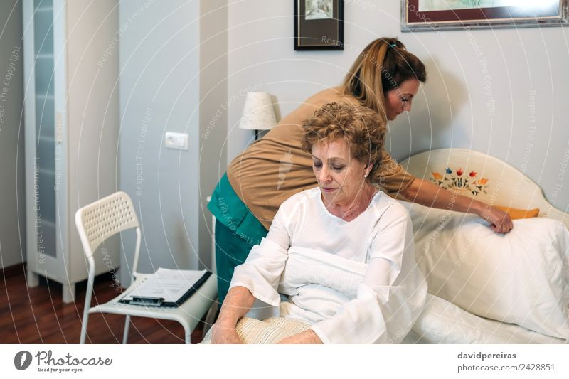 Caregiver accommodating pillow to elderly patient Health care Illness Medication House (Residential Structure) Lamp Chair Doctor Hospital Human being Woman