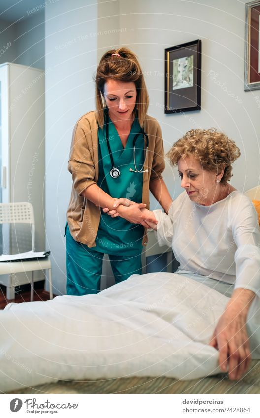 Caregiver helping elderly patient to get out of bed Woman Human being Old Adults Lifestyle Health care Authentic Illness Medication Doctor Self-confident Mature
