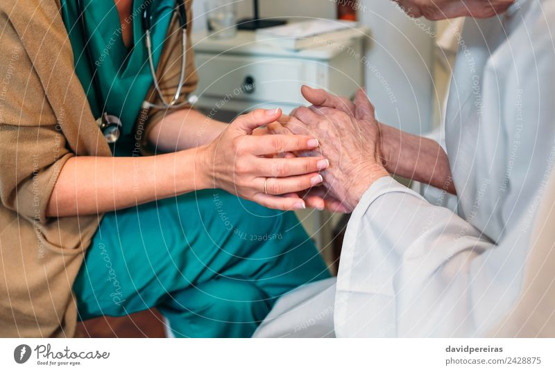 Doctor giving encouragement to elderly patient Illness Medication Hospital To talk Human being Woman Adults Hand Old Authentic Friendliness Trust Compassion