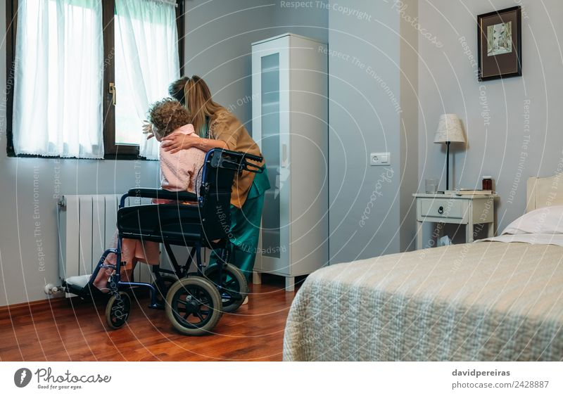 Caregiver with elderly patient in a wheelchair in front of window Lifestyle Health care Illness Medication Doctor Hospital Human being Woman Adults Slippers Old