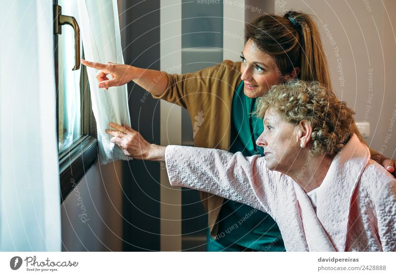 Caregiver showing the view through the window to elderly patient Lifestyle Health care Illness Medication Doctor Hospital Human being Woman Adults Old Smiling